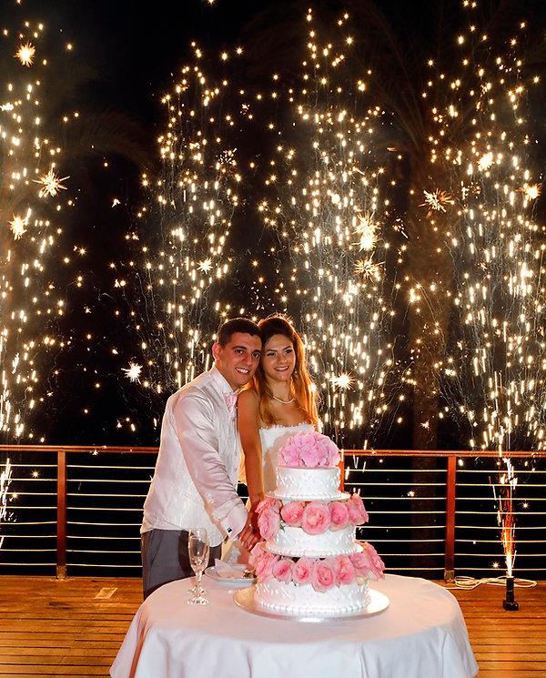 Newly married couple  cutting wedding cake on their wedding party background heavy beautiful fireworks with lots of stars | wedding photo ideas protaras cyprus - Beach weddings
