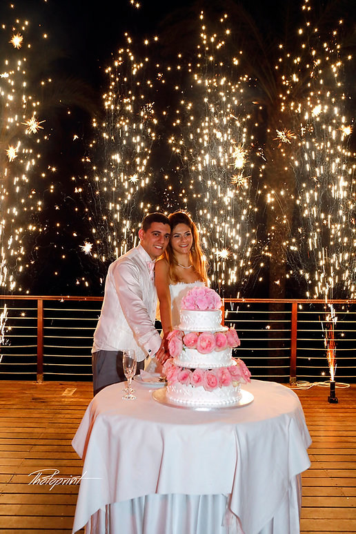 Newly married couple  cutting wedding cake on their wedding party background heavy beautiful fireworks with lots of stars | budget wedding photographer cyprus, cheap but good wedding photographers cyprus, famous wedding photographer cyprus
