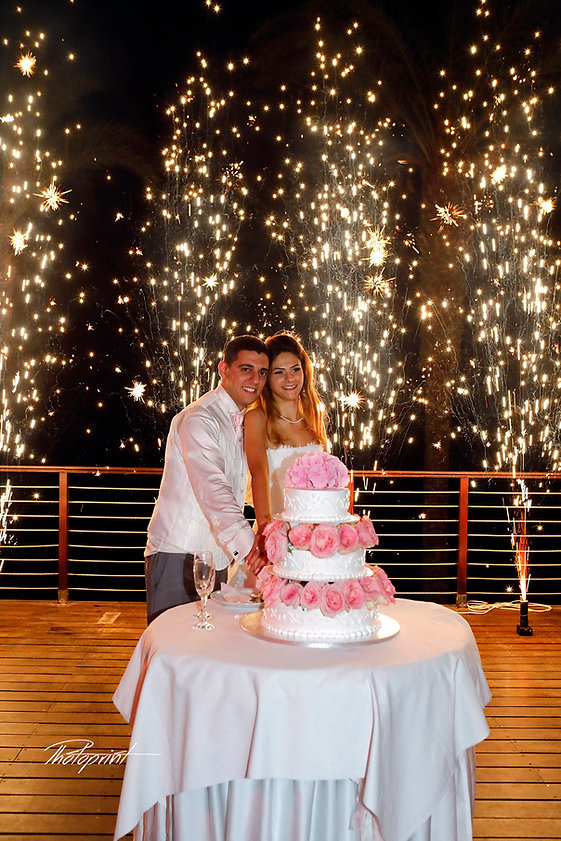 Newly married couple  cutting wedding cake on their wedding party background heavy beautiful fireworks with lots of stars   best cyprus wedding photographers protaras, wedding photographers in protaras, wedding protaras photographers cyprus