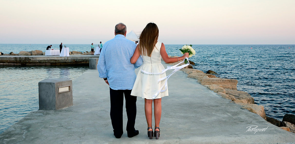 The  bride in a white dress holding a bouquet coming with her father for the wedding ceremony  ( back view ) Mediterranean Sea on background | wedding venues photographer in limassol cyprus, wedding limassol photographers