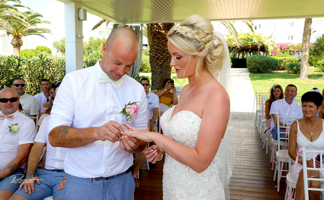 Romantic picture of Joe wears  the ring to Ashley during wedding ceremony | Nissi Beach Resort ayia napa  wedding photographers, ceremony, bride, photograph, woman, wedding.