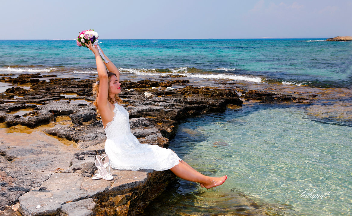 Gorgeous bride in wedding dress with bouquet of flowers posing by the sea |  ayia napa pre wedding photography, ayia napa professional photography wedding, ayia napa professional wedding photo