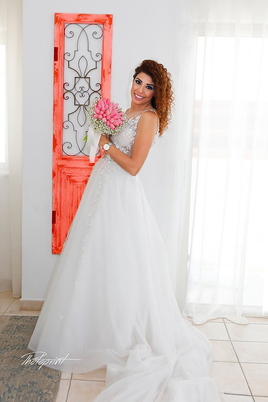 Gorgeous bride in wedding dress with bouquet of flowers posing, red door on the background