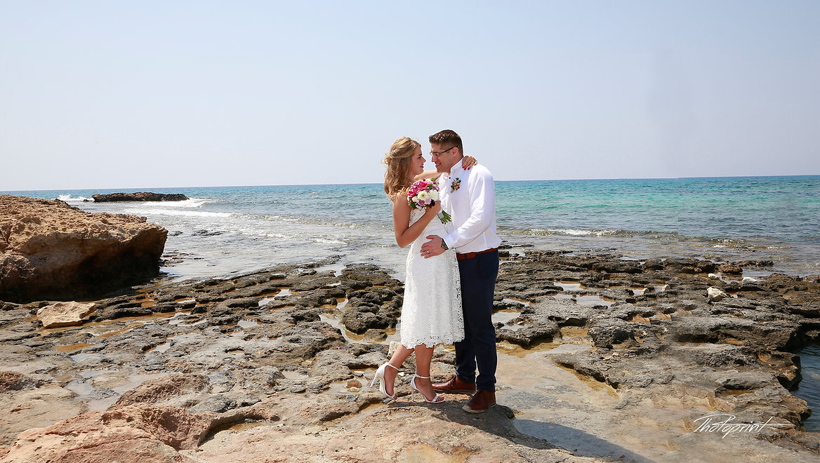 Handsome groom holds in hands his aristocratic blonde bride, the blue Mediterranean Sea on background | cheap wedding photographer in ayia napa, cheap wedding photographers in ayia napa, cheap wedding photography agia napa cyprus, city hall ayia napa wedding photography