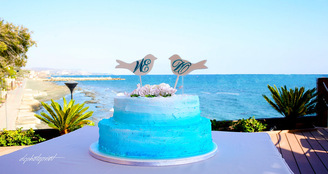 Beautiful wedding cake. Mediterranean Sea on background | photographers in limassol  venues, cyprus cheap venues wedding photographers limassol