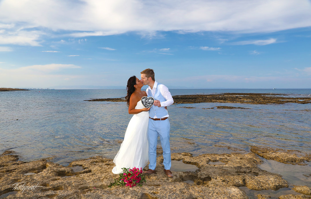 Atilla and Sandra kissing at the Agia Triada beach in sunset | best wedding photographer cost
