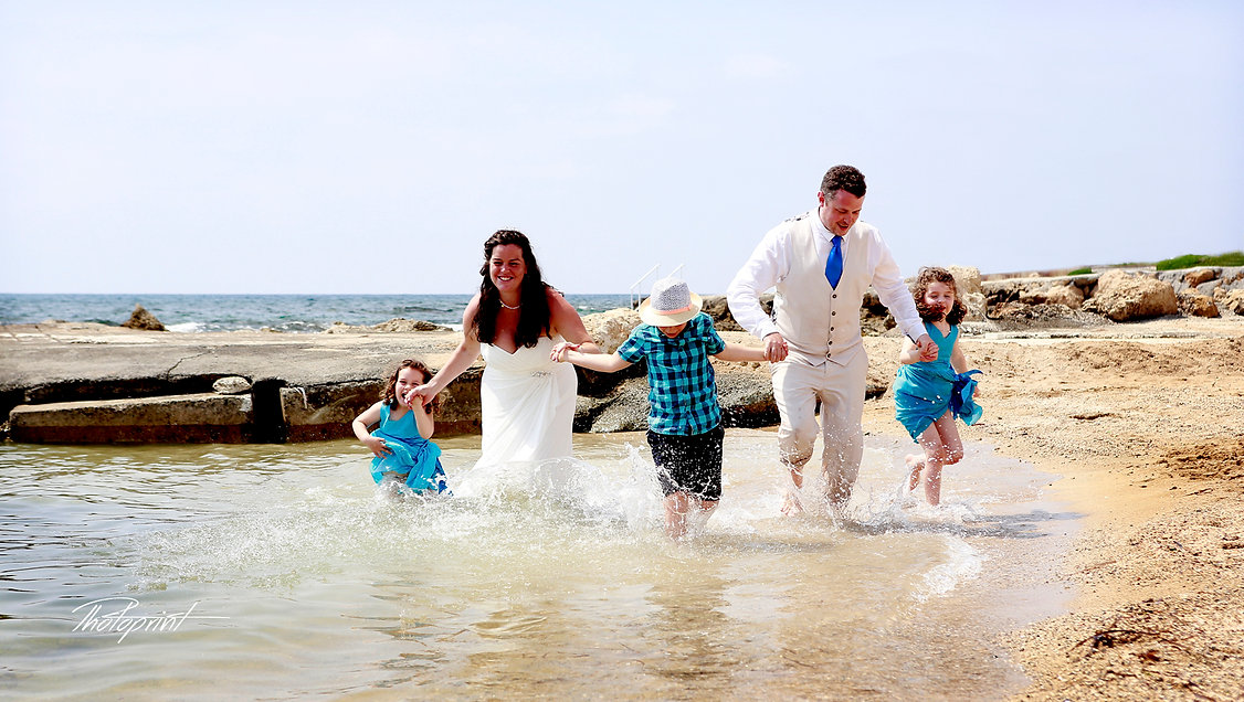 Beautiful couple on the paphos beach with their children having fun at the seaside | professional wedding photo cyprus,cyprus wedding photographer cheap, cheap wedding photographers cyprus