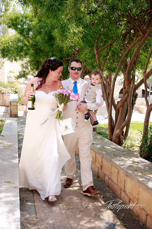 the bride and groom holding their little child are walking towards the white bus | cyprus wedding photographers yeroskipou, Yeroskipou best weddings abroad, wedding photo ideas Geroskipou cyprus