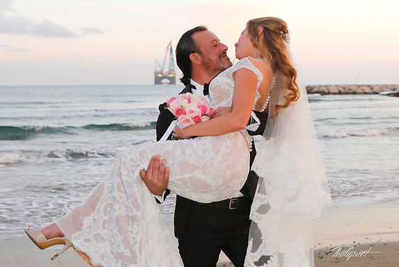 Handsome groom holds in hands his aristocratic blonde bride, the blue Mediterranean Sea on background  |  beach weddings larnaca, Beach Weddings Packages larnaca, Beach Weddings Packages larnaca cyprus, best photographers in larnaca, Civil ceremony at Larnaka town hall