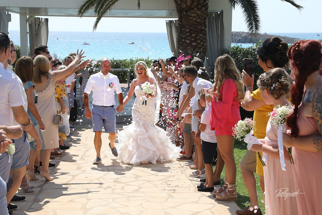 Guests showered newlyweds with colorful confetti after wedding atNissi BeachResort in Ayia Napa, Cyprus | best cyprus wedding photographers in nissi beach resort in ayia napa
