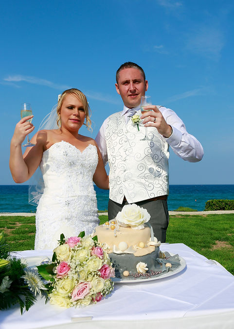 Bride and groom holding champagne glasses, celebrating.Mediterranean Sea on background | best cyprus wedding photographers protaras, cyprus wedding photographer protaras