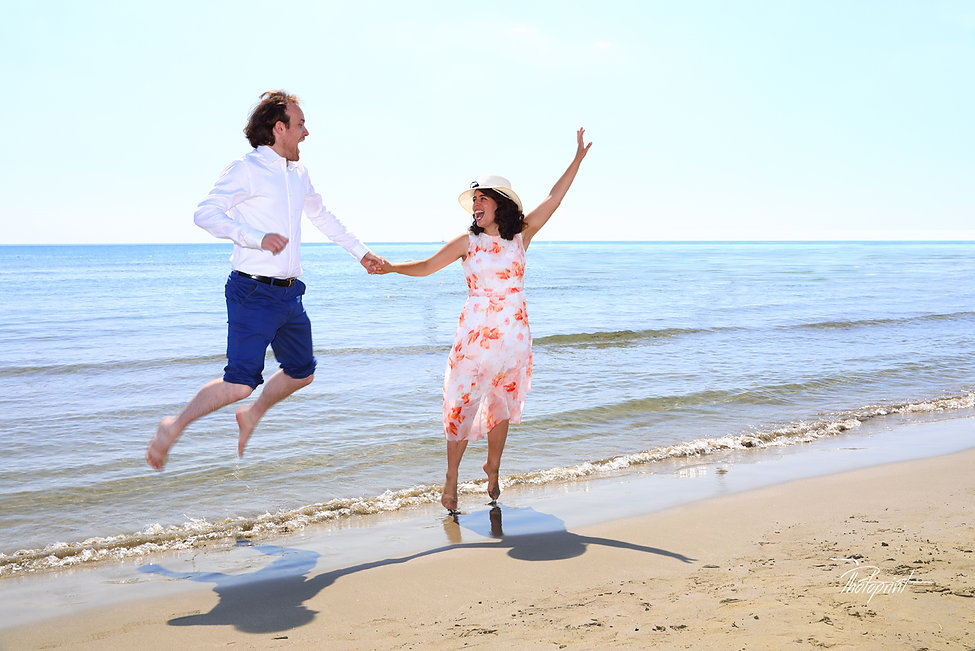 Couple jumping on the sea beach, celebrate  after the wedding
