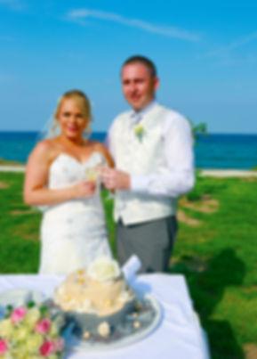 Bride and groom holding champagne glasses, celebrating.Mediterranean Sea on background | photographer in protaras, wedding photo ideas protaras cyprus