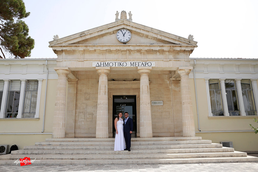 Couple standing outdoor the town hall Paphos holding hands after the wedding | israeli wedding photographers paphos prices, israeli best wedding photographers in cyprus
