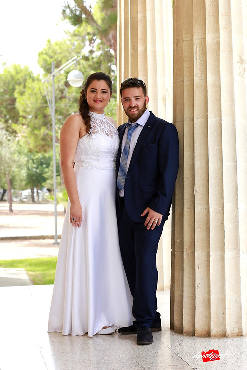 Beautiful israeli couple standing outdoor the town hall Paphos holding hands after the wedding | israeli paphos wedding photographer, sraeli wedding photos ayia napa cyprus