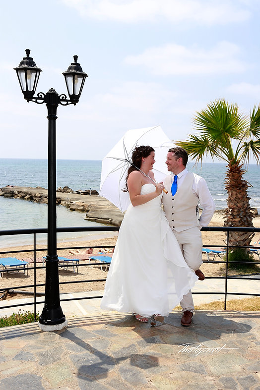 Handsome groom holds in hands his aristocratic blonde bride, the blue Mediterranean Sea on background | wedding venues Geroskipou cyprus, best wedding venue Geroskipou, wedding venues in Geroskipou cyprus
