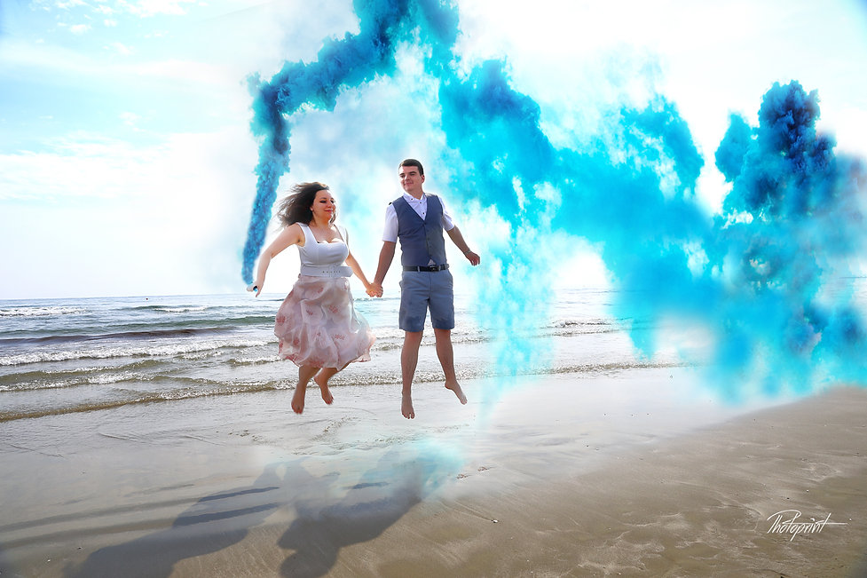 Beautiful young and attractive Couple kissing and celebrating holding blue smoke grenade, bomb by the beach at Larnaca, after the wedding.