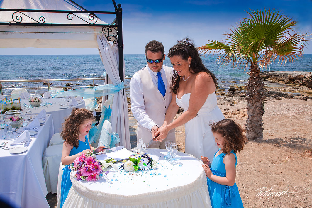 Beauty bride and handsome groom are cutting a wedding cake in kefalos tourist village Paphos.The blue Mediterranean Sea on background | city town hall marriage at paphos,wedding photographer paphos prices, maried in paphos municipality cyprus