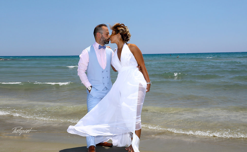Groom kissing his bride by beach at Larnaca. cyprus wedding photgrapher