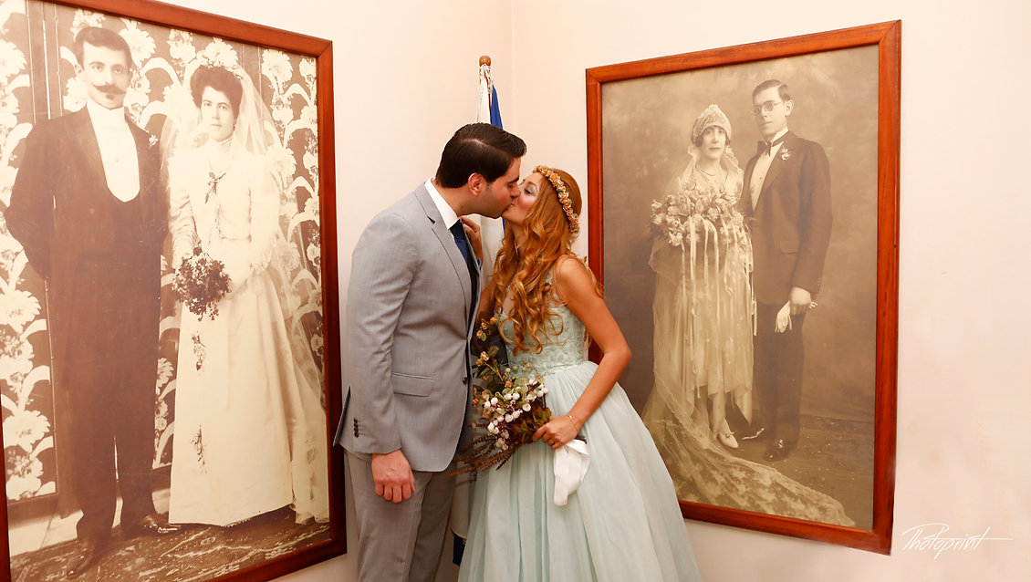 Handsome young groom kissing his wife close to old big photoς on the wall | Bridal wedding photographer nicosia, nicosia destination photographer, civil marriage in nicosia cyprus