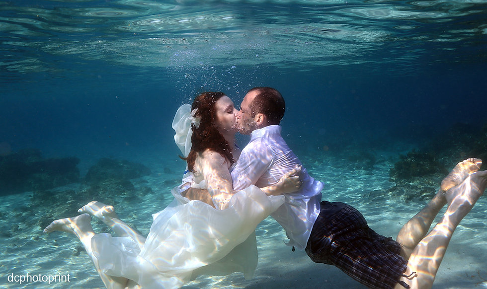Trash the dress. Bride and groom are taking a swim underwater. Bride wears wedding dress | cyprus cheap wedding photographers price