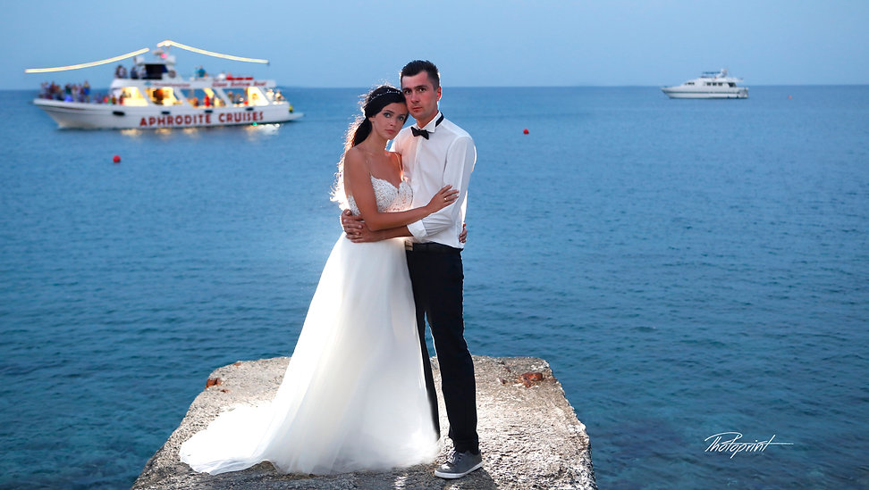 Handsome groom holds in hands his aristocratic blonde bride, the blue Mediterranean Sea on background - wedding portfolio