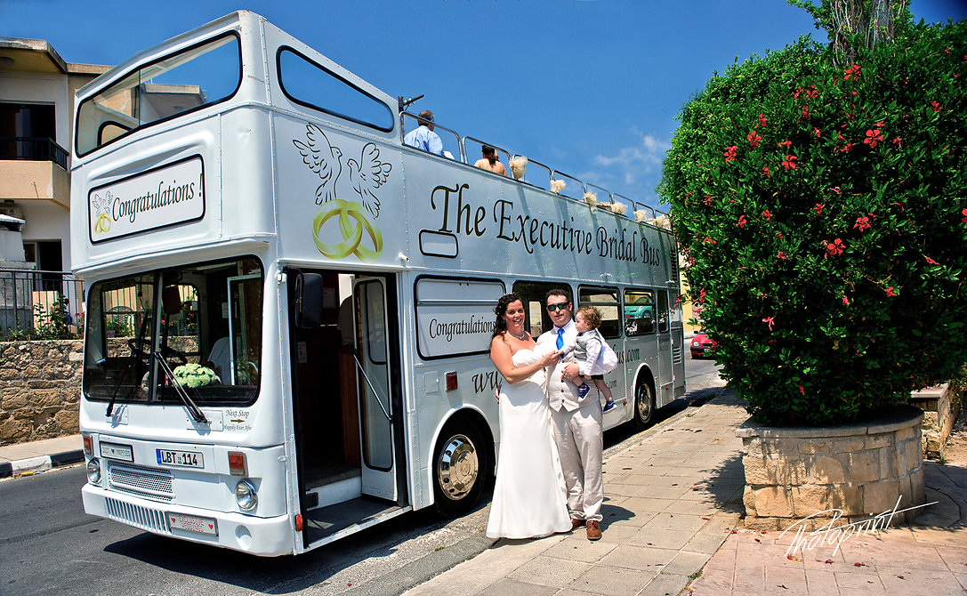 photo with the bride and groom with their little child are standing next to Executive Bridal Bus | cyprus wedding photographers Geroskipou, wedding photographer in Geroskipou cyprus, photographers in Geroskipou