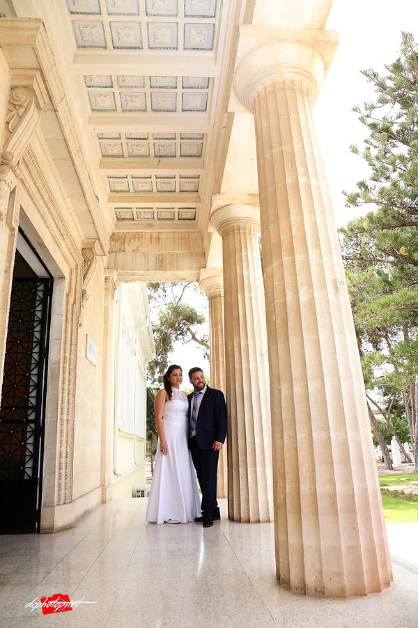 Beautiful israeli couple standing outdoor the town hall Paphos holding hands after the wedding | israeli wedding photographers paphos prices, best israeli wedding photographer larnaca cyprus