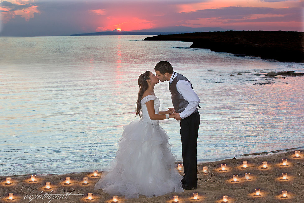 photo of a newlywed couple surrounded by decades of candles by the afternoon on the beach ammos tou Kampouri, ayia napa
