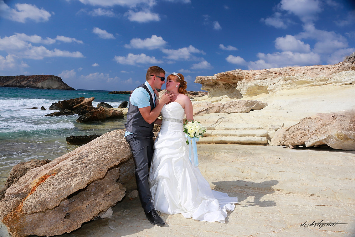 Couple in love sitting near in  Blue beach of Paphos, cyprus | famous wedding photographer photos in Paphos, professional wedding photographers in Paphos