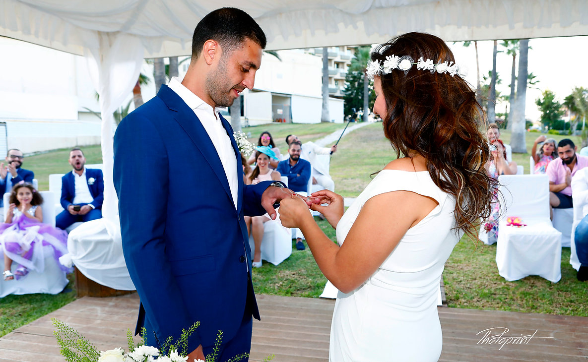 She put her wedding ring on his finger on his in the wedding ceremony   in Golden Bay Beach Hotel, Larnaca  | cyprus wedding larnaca wedding photography prices,