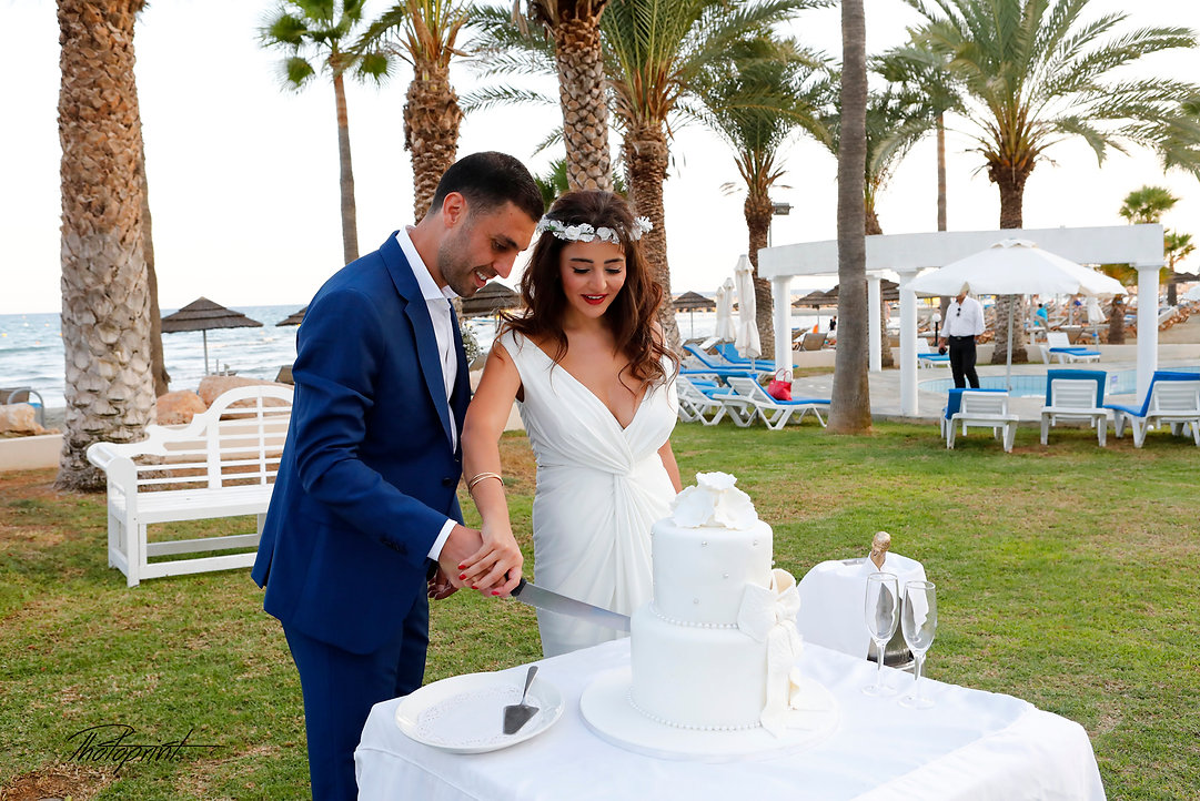 Beauty bride and handsome groom are cutting a wedding cake at reception  in Golden Bay Beach Hotel, Larnaca  | larnaca wedding photo prices , cyprus wedding photographer larnaca | photoprint cyprus
