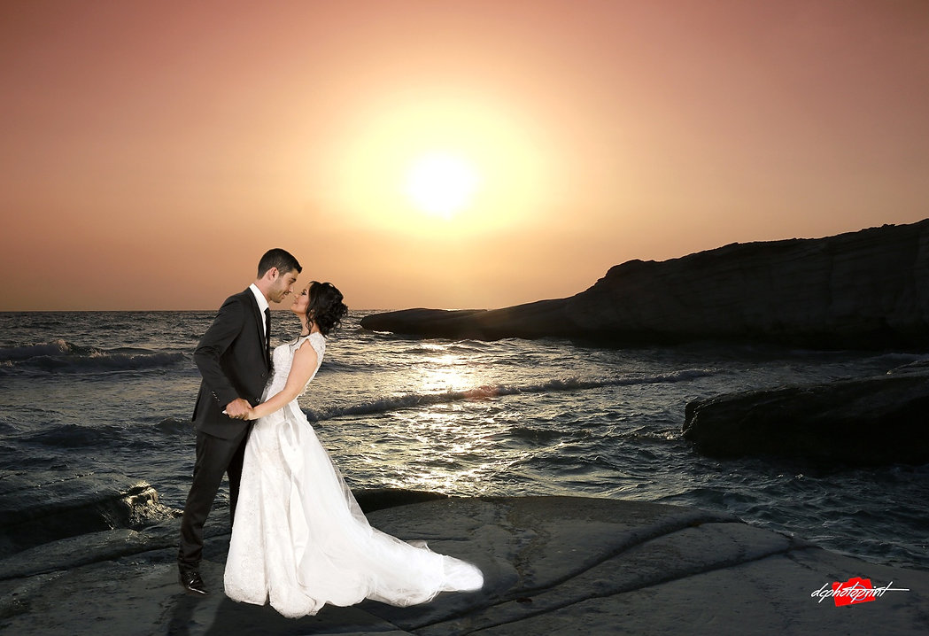 Beautiful and gentle wedding photo session outdoors of the elegant couple, bride in a white dress with veil holding a bouquet and groom in the classic tuxedo costume, romantic portrait  on Paphos beach at sunset | paphos beach hotel wedding photography, wedding venues in paphos cyprus