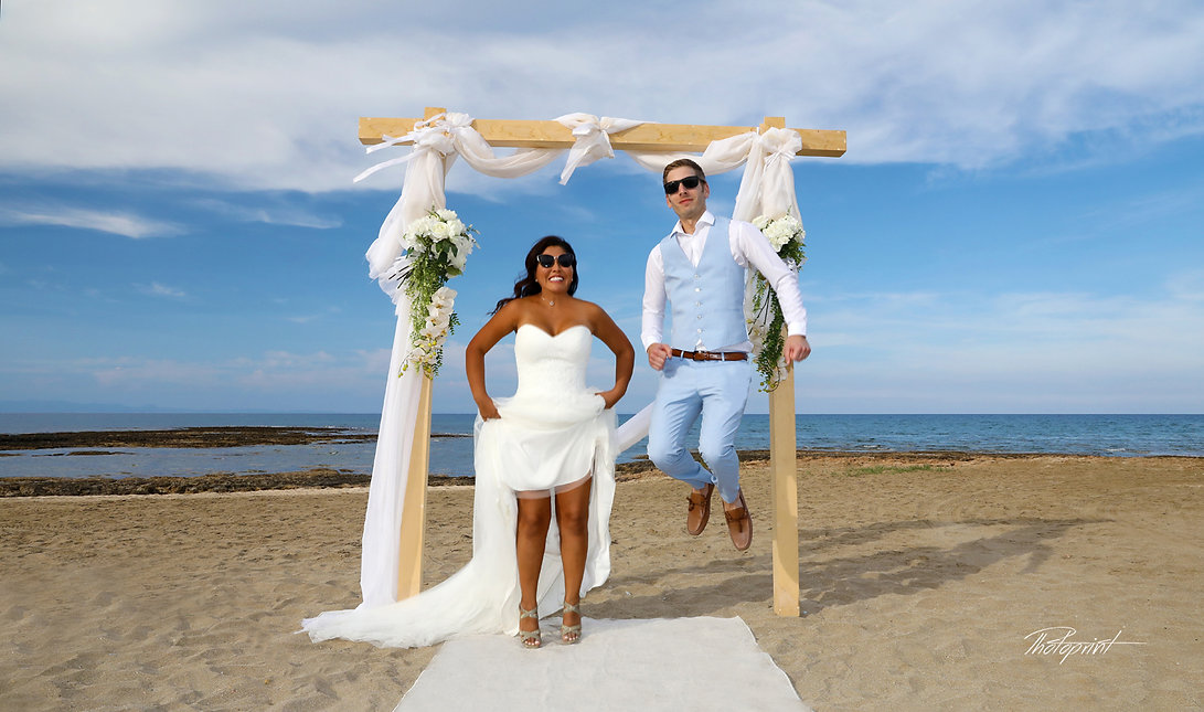 Happy newlyweds jumping up on beach | Agia Triada wedding photography venues