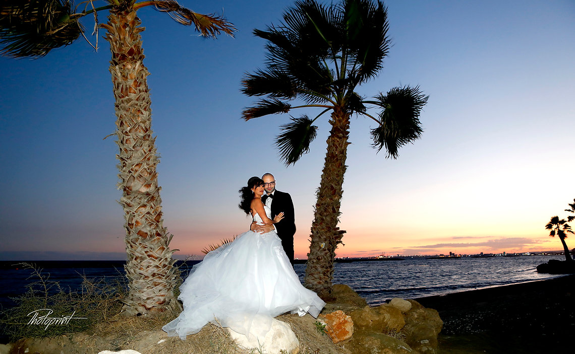 Romantic picture of the marriage couple through two palm trees night | Cyprus Weddings in Larnaca, larnaca civil wedding photographer. larnaca town hall weddings