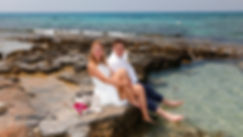 Elegant smiling bride and groom they are sitting on the beach, the blue Mediterranean Sea on background
