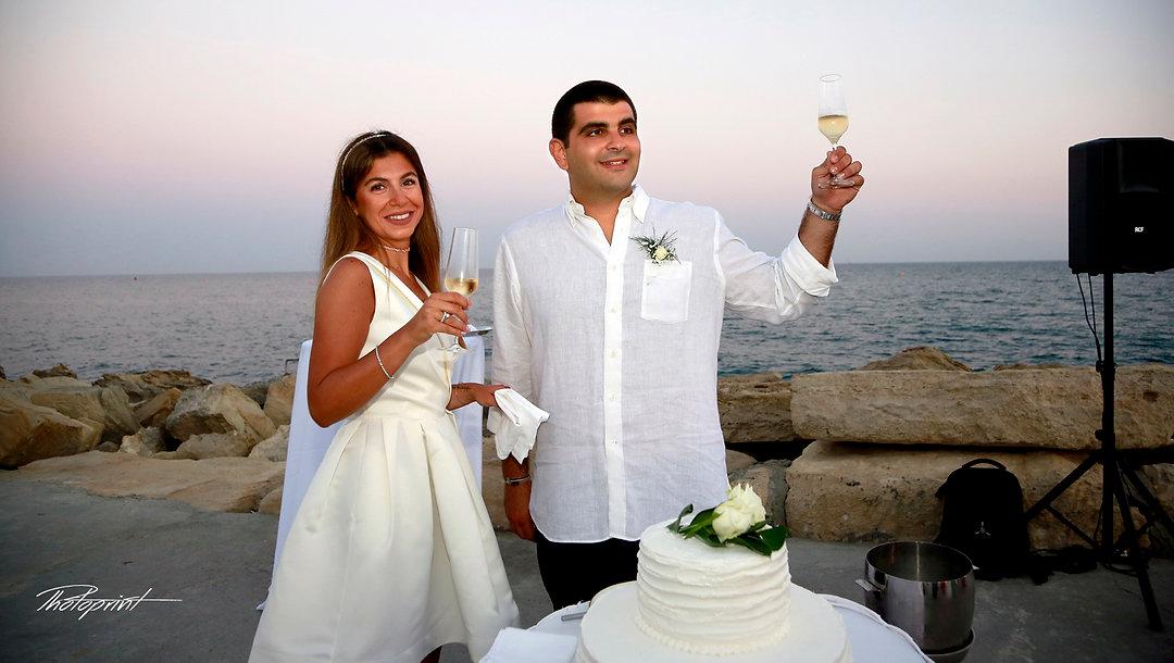 Bride and groom holding champagne glasses, celebrating.Mediterranean Sea on background  | limassol beach hotel wedding photography, civil limassol wedding photography