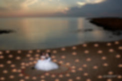 photo of a newlywed couple surrounded by decades of candles at night on the beach ammos tou Kampouri, ayia napa