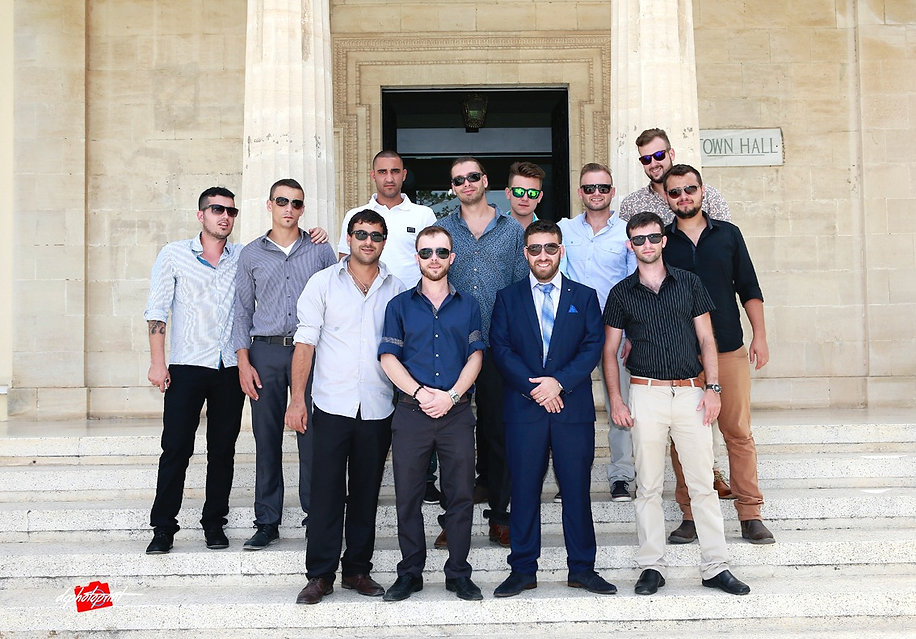the groom together with other guests who wear sunglasses outside of Town Hall Paphos after the wedding | israeli  best wedding photographer in ayia napa cyprus,wedding larnaca photographers
