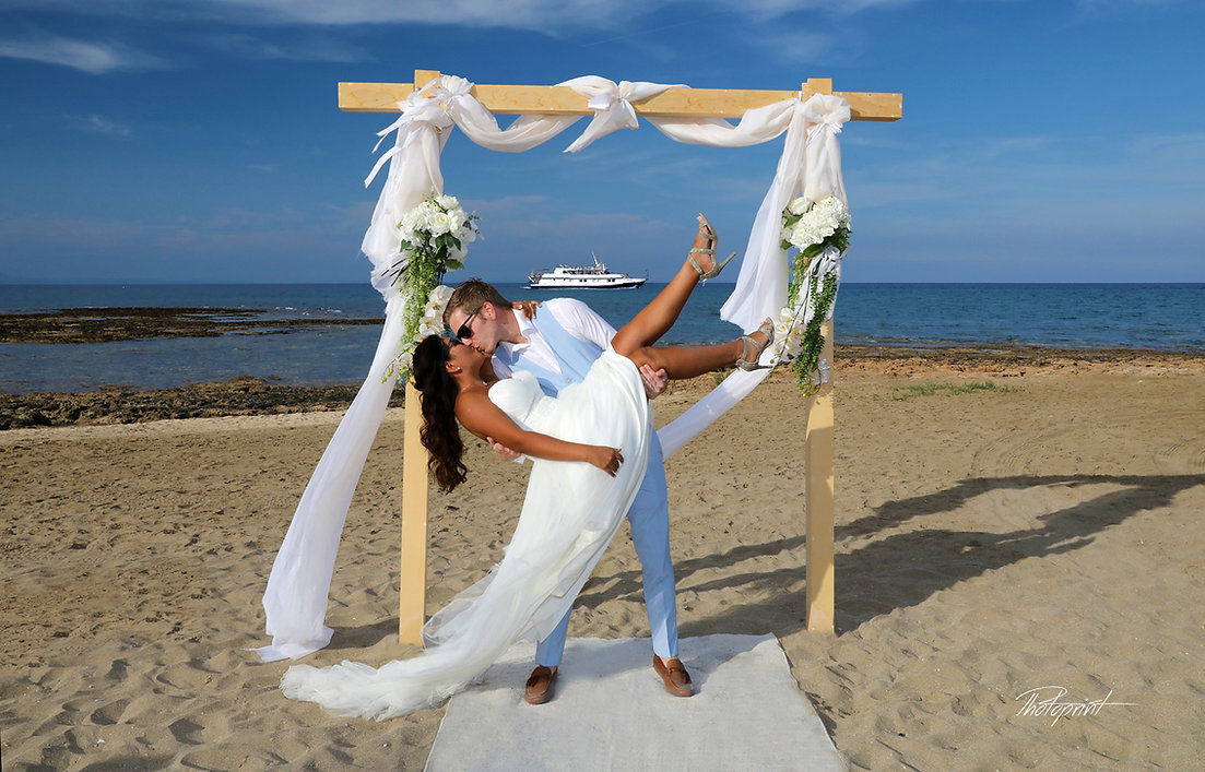 Atilla and Sandra at Beautiful Mediterranean beach with decorated wedding pergola with and white materials prepared for ceremony | Ayia triada wedding photography packages, ceremony, beach, vecation, sea, wedding.