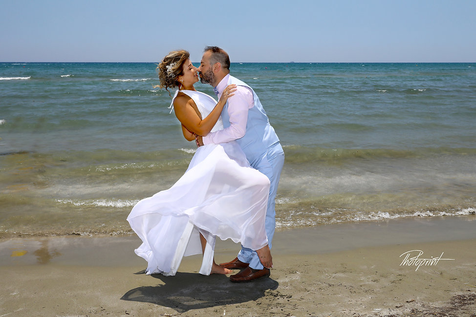 Gorgeous blonde bride and stylish groom celebrating after the wedding by the beach at Larnaca. best wedding photographer in larnaca.