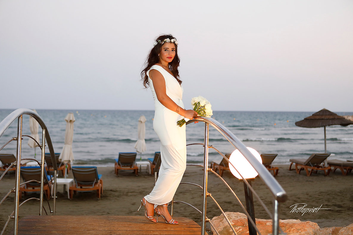 Gorgeous bride in wedding dress with bouquet of flowers posing on the small bridge with a blue sea background | cyprus wedding photographer larnaca,Lebanese weddings in larnaca cyprus,wedding photography municipality larnaca photographers