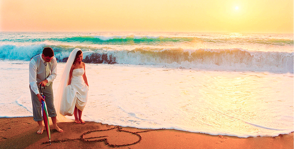 The groom draws a heart on the sand with his umbrella, the bride smiles and the sunset is amazing  wedding portfolio