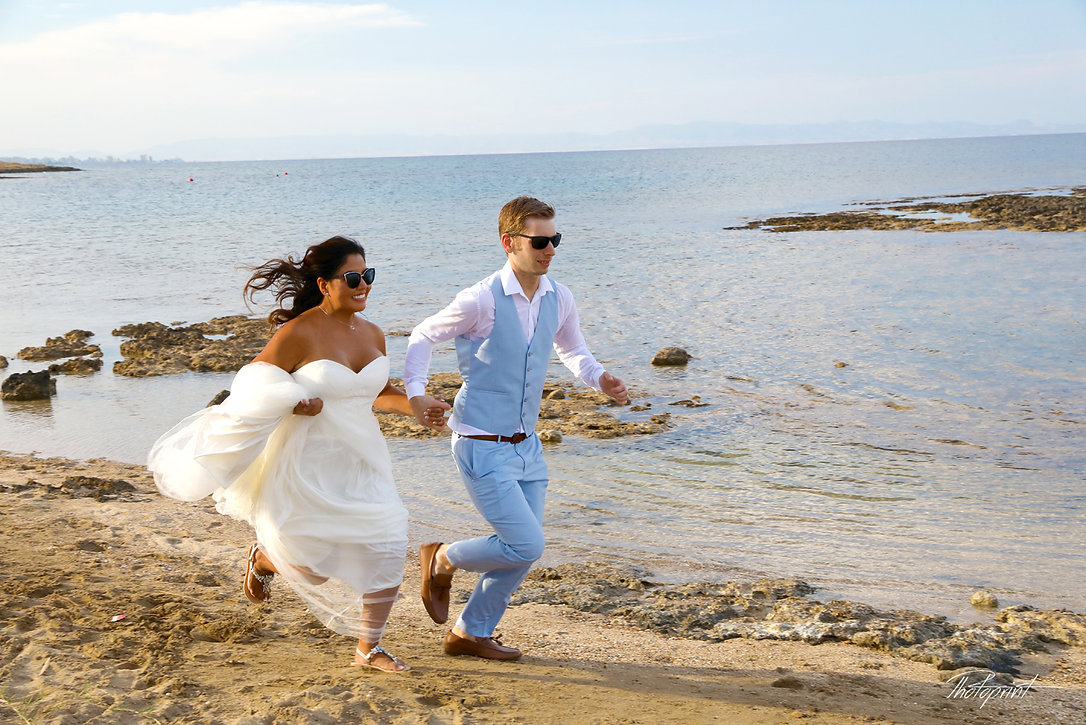 Smiling bride and groom run on seashore | cyprus sunset images wedding photography