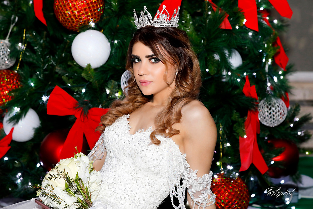 Portrait of beautiful young bride in a luxurious lace wedding dress, in the background the most beautiful Christmas tree.