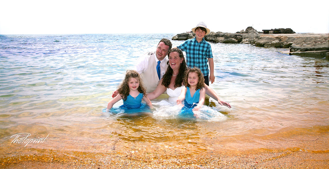 Beautiful couple on the paphos beach with their children having fun at the seaside | paphos wedding photographer, cyprus wedding photographer, photoprint cyprus