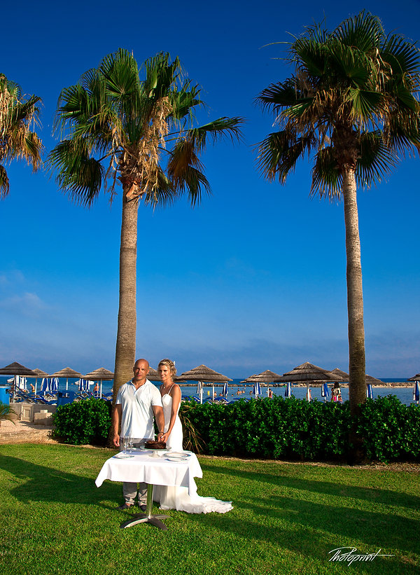 Romantic picture of marriage couple who cut the wedding cake. Two palm trees on the background and a little below the blue sea | best weddings abroad sirens beach, married in ayia Thekla best beach cyprus, cyprus wedding photographer ayia thekla cyprus