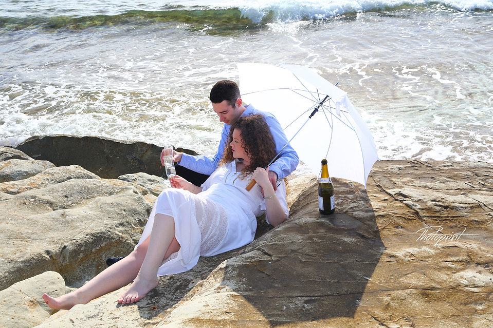 Bride and groom holding champagne glasses, celebrating.Mediterranean Sea on background