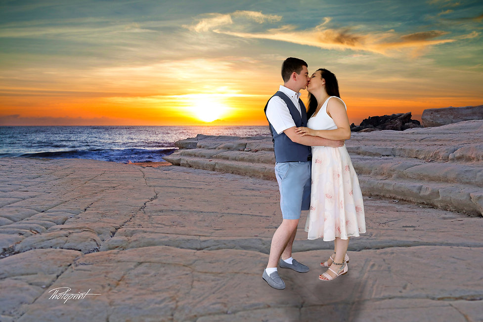 Handsome young groom kissing his wife by the beach on sunset at Paphos after the wedding.