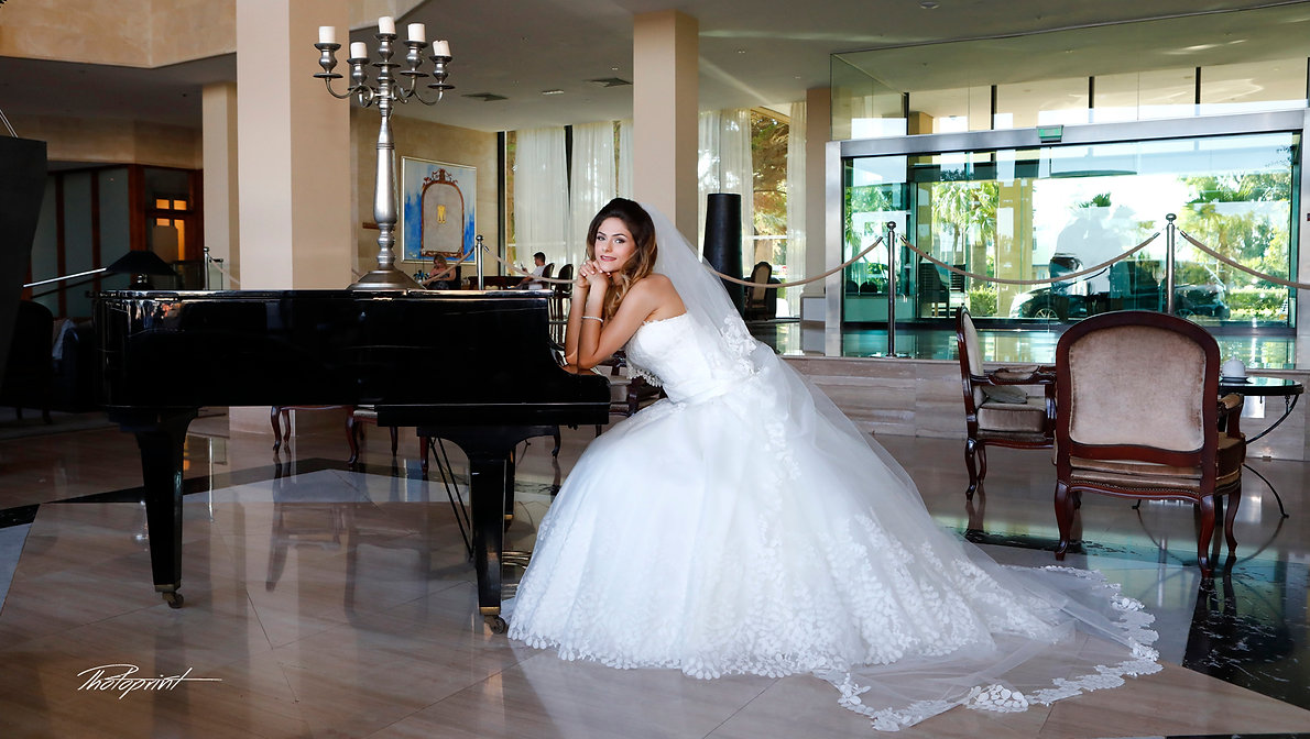 Portrait of beautiful young bride ( Mireille ) in a luxurious lace wedding dress. She sits on a black piano indoors in Grecian Park Hotel at Protaras, cyprus | protaras  best wedding photographer photography, protaras  best wedding photography, cyprus protaras wedding photography  cost